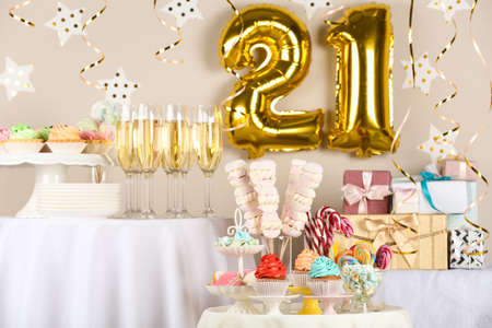 Dessert table in room decorated with golden balloons for 21 year birthday party Reklamní fotografie
