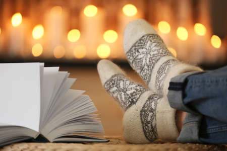 Woman wearing woolen socks relaxing on pouf against blurred background, closeup. Winter atmosphere