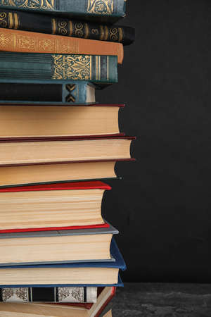 Stack of hardcover books on grey stone table against black background