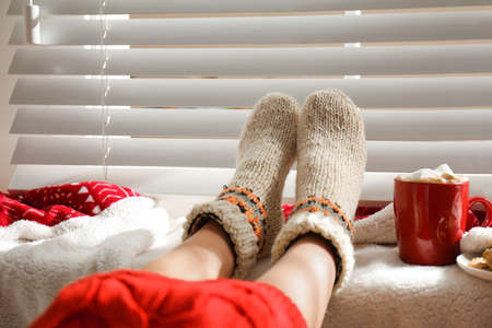 Woman with cocoa wearing knitted socks at home, closeup. Warm clothes Stock Photo
