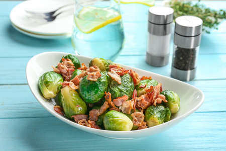 Tasty roasted Brussels sprouts with bacon on light blue wooden table