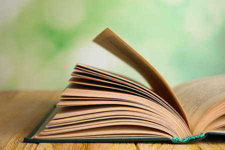 Open book on wooden table against blurred green background, closeup Stock Photo
