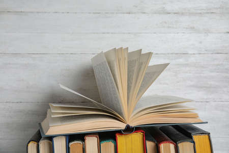 Stack of hardcover books on white wooden background