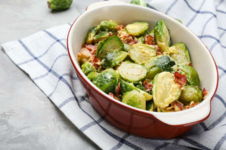 Delicious Brussels sprouts with bacon in baking pan on grey table, closeup