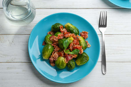 Tasty roasted Brussels sprouts with bacon on white wooden table, flat lay