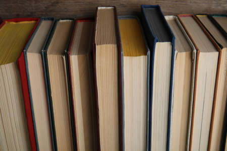 Stack of hardcover books on wooden background