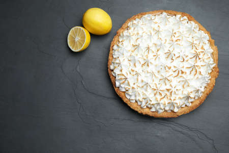 Flat lay composition with delicious lemon meringue pie on black table, space for text