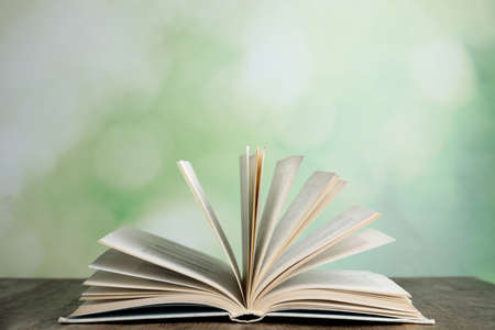Open book on wooden table against blurred green background Stock Photo