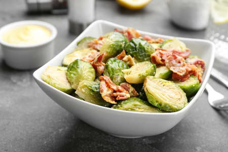 Delicious cooked Brussels sprouts with bacon served on grey table, closeup
