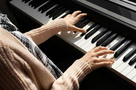 Young woman playing piano at home, closeup