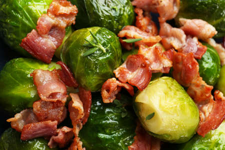 Tasty cooked Brussels sprouts with bacon as background, closeup