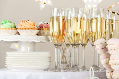 Candy bar with delicious treats and glasses of champagne for birthday party