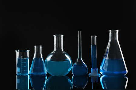Cristalería de laboratorio con líquidos azules sobre fondo negro