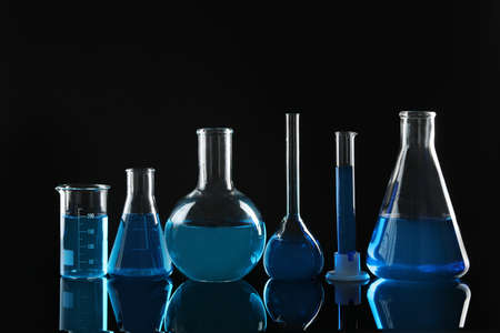 Laboratory glassware with blue liquids on black background
