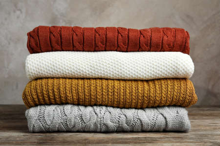 Stack of warm clothes on wooden table against grey background. Autumn season 版權商用圖片 - 132114932