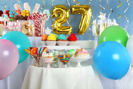 Dessert table in room decorated with golden balloons for 27 year birthday party Stok Fotoğraf