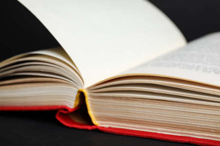 Closeup view of open book on black background Stock Photo
