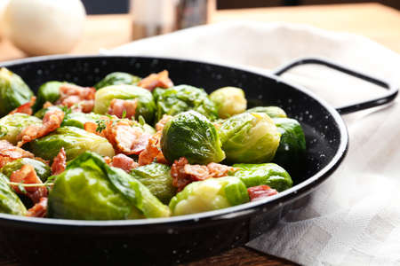 Tasty roasted Brussels sprouts with bacon on wooden table, closeup