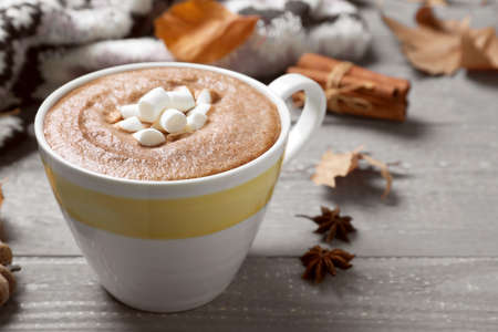 Cup of hot drink on grey wooden table, closeup. Cozy autumn atmosphere