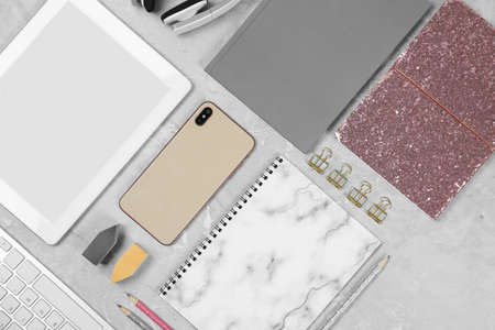 Flat lay composition with tablet, phone and notebook on grey marble table. Designer's workplace
