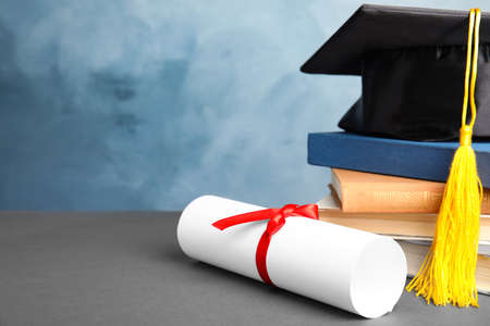 Graduation hat, books and student's diploma on grey table against light blue background. Space for text