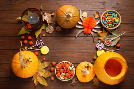 Flat lay composition with pumpkin head Jack lantern and Halloween treats on wooden background. Space for text