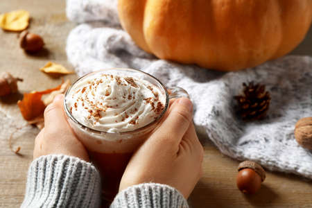 Woman with cup of pumpkin spice latte at wooden table, closeup