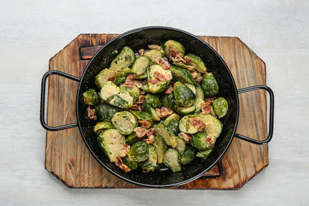 Delicious cooked Brussels sprouts with bacon in pan on white table, top view