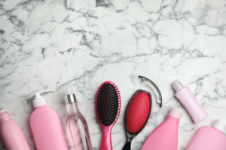 Flat lay composition with hair cosmetic products and tools on marble background. Space for text