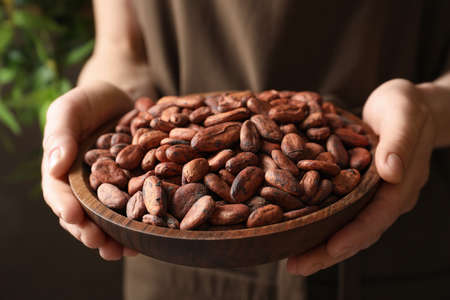 Woman holding wooden bowl of cocoa beans, closeup view Stock fotó