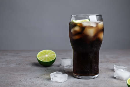 Refreshing soda drink, ice cubes and lime on table against grey background, space for text