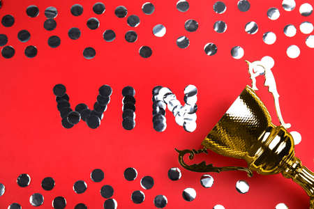 Gold trophy cup and word WIN made with silver confetti on red background, flat lay
