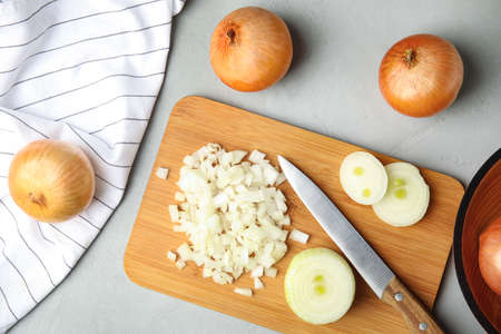 Flat lay composition with chopped and whole onions on grey table