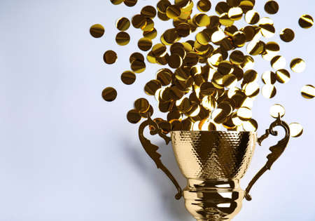 Gold trophy cup and confetti on white background, top view