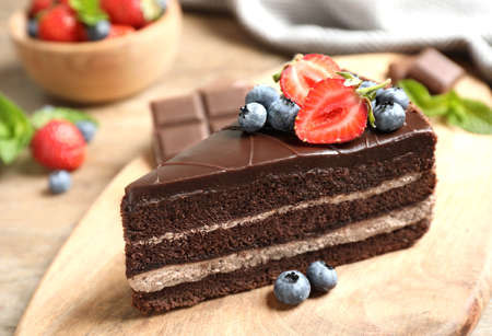 Delicious fresh chocolate cake with berries on wooden table, closeup Stock fotó