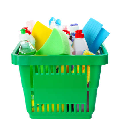Green shopping basket with different household chemicals on white background
