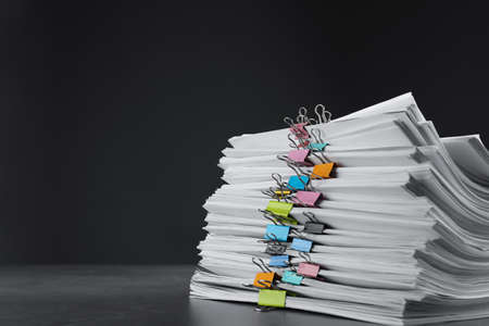 Stack of documents with binder clips on grey stone table against black background, space for text