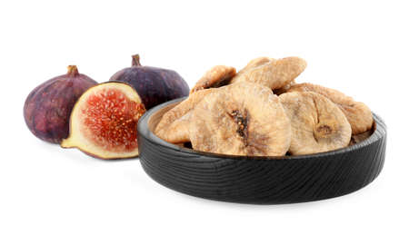 Black wooden plate of dried figs and fresh fruits on white background