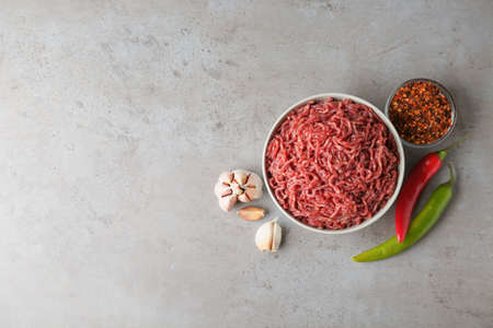 Flat lay composition with fresh raw minced meat on light table. Space for text