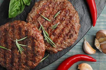 Grilled meat cutlets for burger on blue wooden table, top view Stock fotó