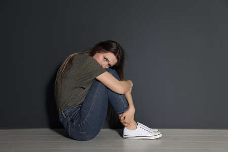 Upset young woman sitting on floor near grey wall. Space for text
