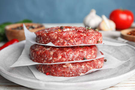 Raw meat cutlets for burger on white wooden table, closeup