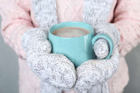 Woman with knitted mittens holding cup of delicious cocoa drink, closeup Stock fotó