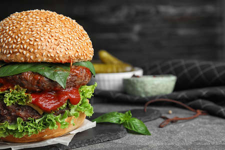 Delicious burger with meat cutlets on grey table. Space for text