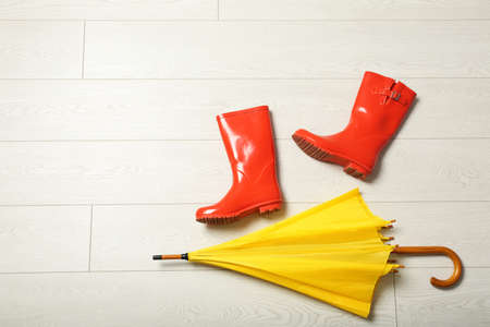 Color umbrella and rubber boots on wooden floor, flat lay. Space for text