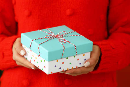 Woman in red sweater holding Christmas gift, closeup