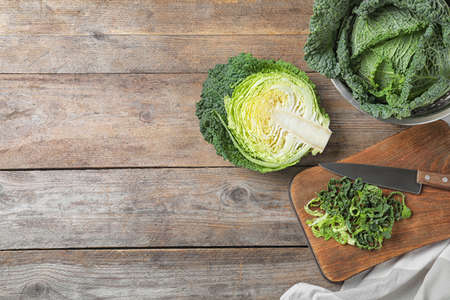 Flat lay composition with fresh green savoy cabbage on wooden table. Space for text