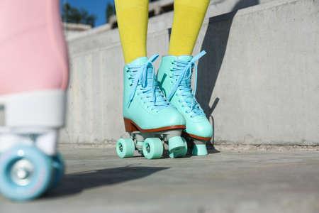 Mujer joven con patines retro en la ciudad en un día soleado, primer plano