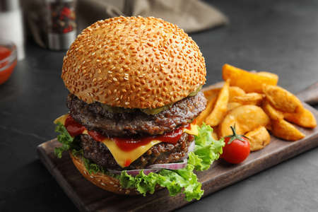 Delicious burger with meat cutlets on black table, closeup