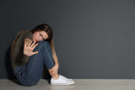 Young woman making stop gesture while sitting on floor near grey wall. Space for text